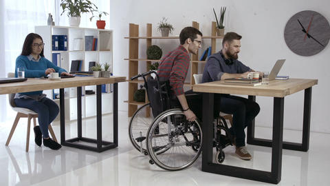 Disabled worker and colleagues working in office Footage