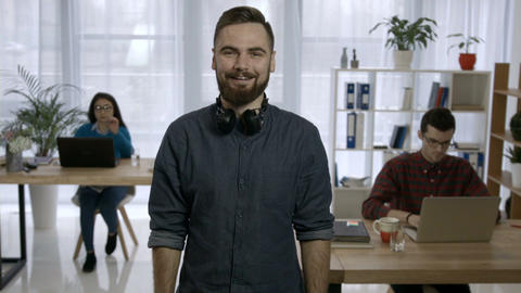 Portrait of young hipster with beard at workplace Footage