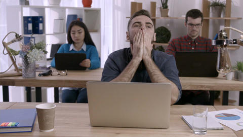 Stressed man working at desk in creative office Footage