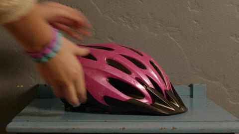 Picking up a pink helmet, closeup Footage