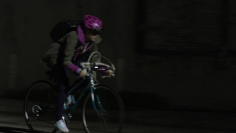 Young woman rides bike quickly through alley Footage
