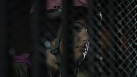Girl in bicycle helmet waits behind metal gate Footage
