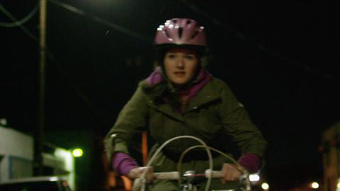 Teenage girl rides bicycle on city street at night 2 Footage