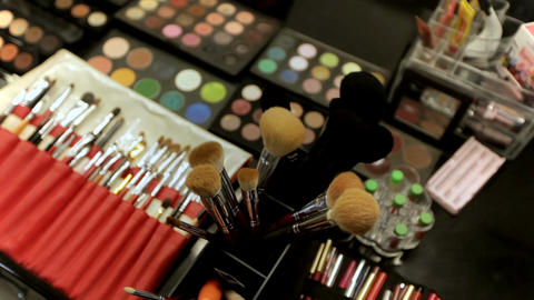 Professional cosmetics makeup artist on the table in the studio. Multicolored Footage