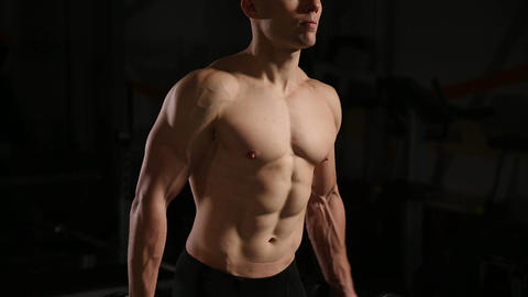 Athletic shirtless young sports man - fitness model holds the dumbbell in gym Footage