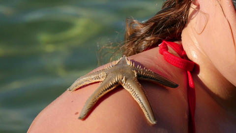 Girl playing with small live sea star she found in the sea Live Action