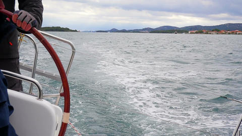 Skipper turning sailing boat in right direction turning steering wheel Footage
