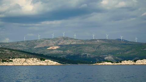 Wind power plants at Croatian coastline shot from sailing boat in Adriatic sea Footage