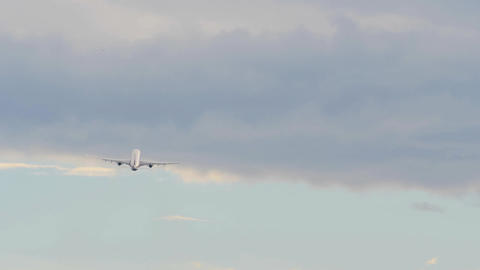 Airliner gains height in sunset cloudy sky Footage