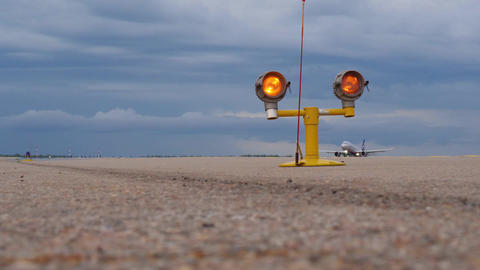 Yellow runway guard lights against jet airliner rising in stormy sky Footage