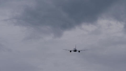 Silhouette of passenger jetliner flying away in stormy sky Footage