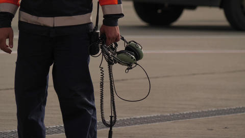 Technician from airport ground support team holds headset in the hand. Close up 画像