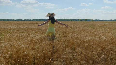 Woman in flower diadem and yellow dress spins around on golden wheat field at Footage