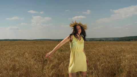 Woman in wheat crown and yellow dress spins round on golden wheatfield at sunny Footage