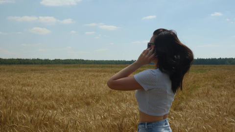 Long-haired woman talks on smartphone while walking on goldish wheatfield Live Action