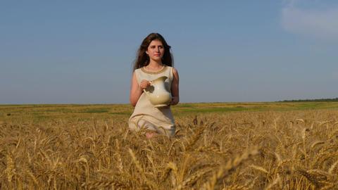 Woman in linen dress carries a jug walking among ripe wheat ears Footage