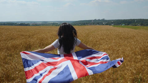Woman in jeans shorts runs on ripe wheat field with UK flag - Union Jack Live Action