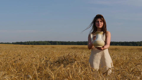 Woman in linen dress holds a jug to the camera standing at goldish wheatfield Footage