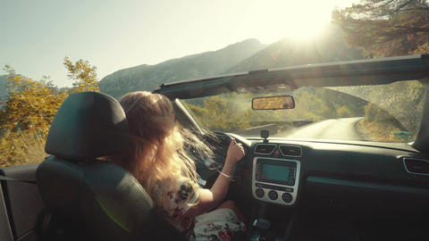 Woman drives convertible car on winding road and wind blows through her hair Footage