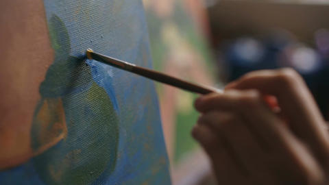 Close-up of artist woman's hand with brush painting still life picture on canvas Live Action