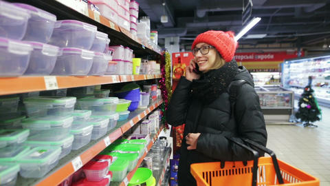 A young modern girl is shopping at a supermarket and talking on her cell phone Footage
