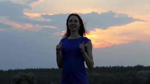An attractive woman smiles and shows thumb up gestures outdoors in slo-mo Footage
