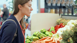 Young woman shopping in grocery store. Standing in vegetable department choosing Footage