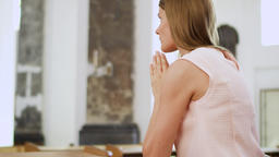 Young devoted religious woman praying in catholic church. Faithful catholic at Footage