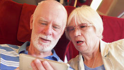 Senior couple in high-speed international train using smartphone. Active modern Footage