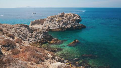 Rocky Coast Of Mykonos Island, Greece. Yacht slowly moving On The Background Footage