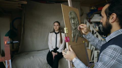 Sculptor creating sculpture of human's face on canvas while young woman posing Footage