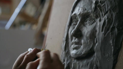 Close-up of Sculptor creating sculpture of woman's face on canvas in art studio Footage