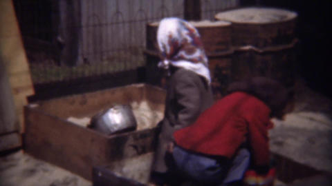 1948: Poor immigrant girl kids playing in industrial sandbox Footage