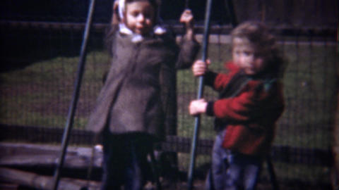 1948: Daredevil kids standing on playground backyard swings Footage