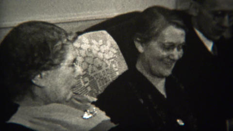 1947: Old women looking at family photos on living room couch Footage