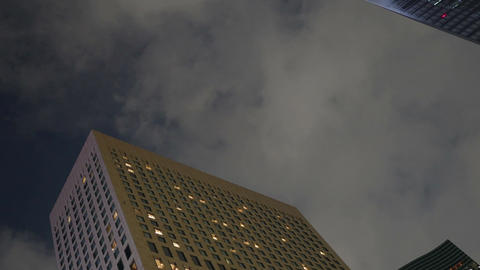 Low angle zoom out of night cloudscape over office buildings Footage