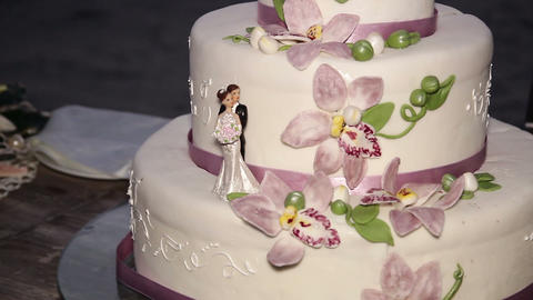 Bride and groom figures on wedding cake Footage