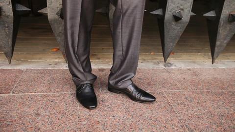 man in black puts black shoe on tip-toe on floor Footage