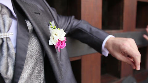 groom in wedding suit with flower snaps fingers Footage