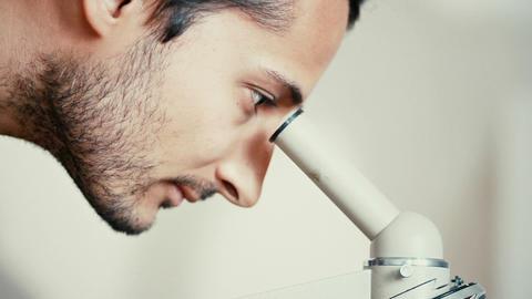 Man lookig through The microscope Footage