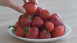 Hand is grabbing strawberries from a plate Footage