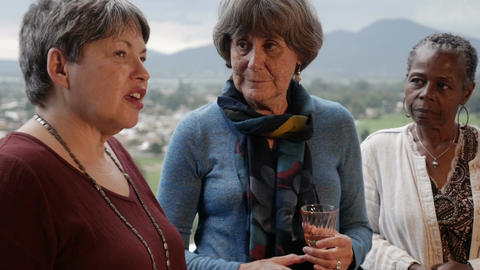 Diverse group of attractive elderly women talking on a balcony with mountain Footage