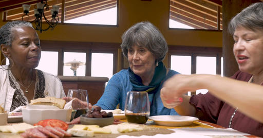 A woman pouring wine for her diverse group of friends over 50 at a party eating Footage
