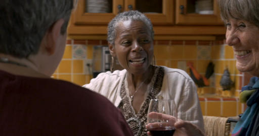 Diverse group of three ladies over 50 drinking wine and laughing at a get Footage
