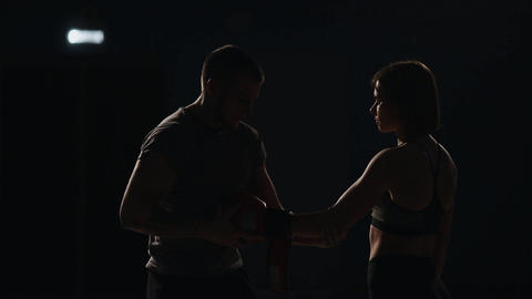 The trainer wears the Boxing gloves to the girl the fighter before the fight Footage