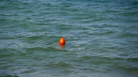 Tutbulent sea with small waves on windy sunset. Small red buoy jumping over Footage