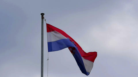 Croatian flag waving in the windy weather. Gray clouds in background bringing Archivo