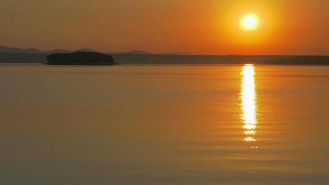 Beautiful orange sunrise morning at seashore. Calm sea reflecting sun at Footage