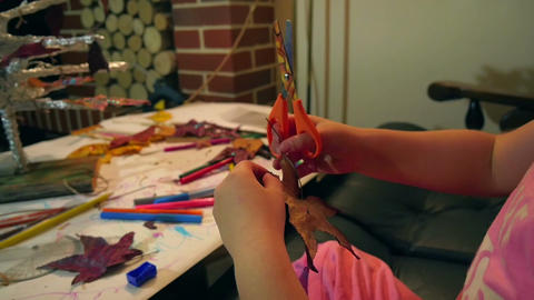 Small girl playing with scissors cutting dry leaves and making decorations. Footage