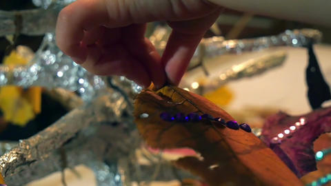 Little girls hand sticking dry leaf decoration on christmas tree branch. Father Footage